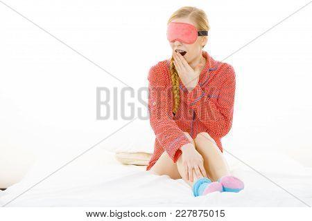Sleep Bedroom Accessories Concept. Sleepy Woman Wearing Pink Eye Band And Pajamas.