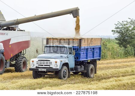 Russia, Poltavskaya Village - September 27, 2015: Unloading Grain From A Combine Into A Truck. Rice