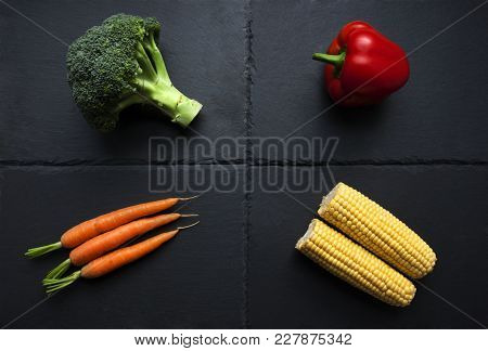 Four Individual Vegetables; Broccoli, Pepper, Carrots, Corn On The Cob On Slate Plate. Organic Produ