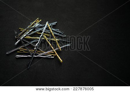 Sparkling Metal Silver Gold And Black Hairpins On A Black Background. A Pile Of Hairpins For Evening