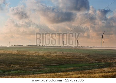 Eco Power, Wind Turbines Stand In The Field, Early Morning, Beautiful Clouds In The Background
