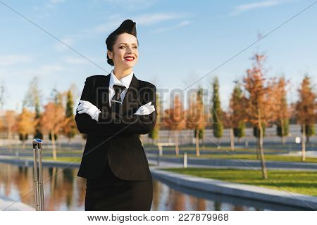 Happy Smiling Woman Stewardess In Uniform Looks Up To The Sky And Waits For Her Flight