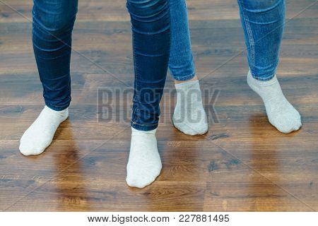 Women Feet Standing On Wooden Floor Wearing Blue Jeans And Light Socks.