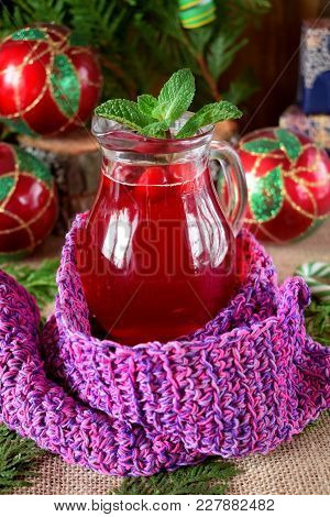 Hot Cranberry Tea In A Glass Jug Surrounded By Christmas Attributes