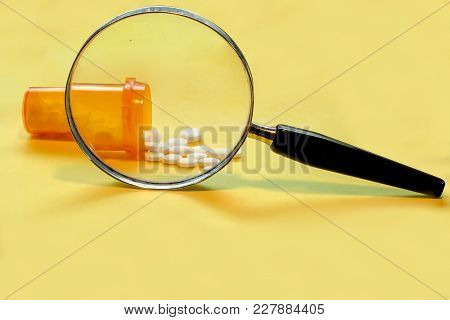 Opioid Crisis - Open Bottle Of Prescription Painkillers With A Magnifying Glass