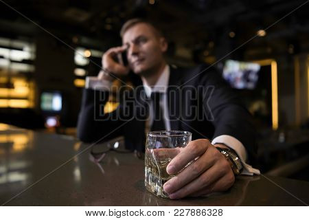 An Elegant, Serious And Concentrated Businessman Holding A Glass Of Cognac, Speaking On The Phone An