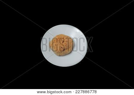 A Cookie With Cracks On A White Plate On Black Background