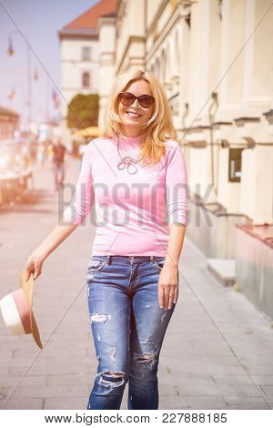 Carefree Trendy Young Woman Walking Down A Street With A Wide Smile In Her Sunglasses Carrying Her S