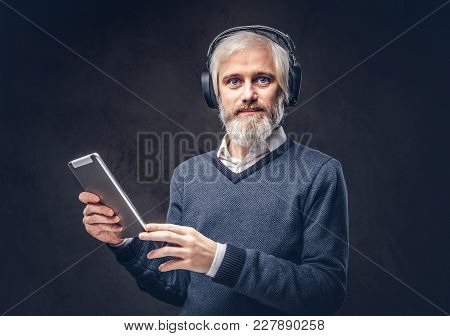 Portrait Of A Handsome Senior Man Using A Tablet With Headphones In A Studio Over A Dark Background.