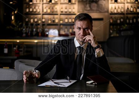 Portrait Of An Elegant, Serious And Concentrated Businessman Holding A Glass Of Whiskey And Looking