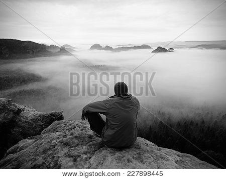 Hiker On The Rocky Peak. Wonderful Daybreak In Mountains, Heavy  Creamy Mist In Deep Valley. Man On