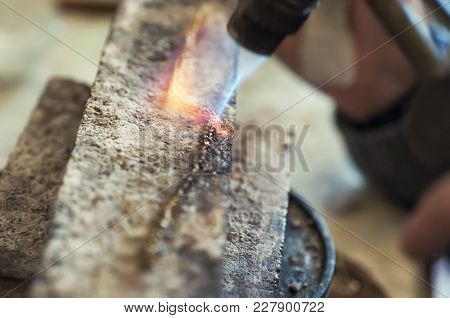 Craft Jewelery Making With Flame Torch. Jeweler Processing Metal Bar By Heating It Up.