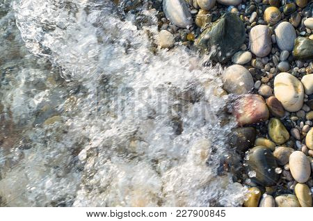Pebble Stones On The Sea Beach On A Warm Summer Day, The Rolling Waves Of The Blue Sea With White Fo