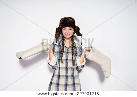 Smiling Young Girl From Russia In A Warm Fur Hat Holds Gray Felt Boots In Hands