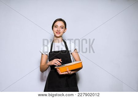 Beautiful Young Woman Chef In Black Apron Preparing Dish