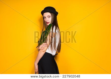 Confident Attractive Girl In Fashionable Black Hat Posing On Yellow Background, Holding A Green Leaf