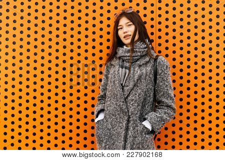 Young Dark-haired Girl Teenager In Gray Coat Posing Against A Background Of Unusual Orange Wall, Str