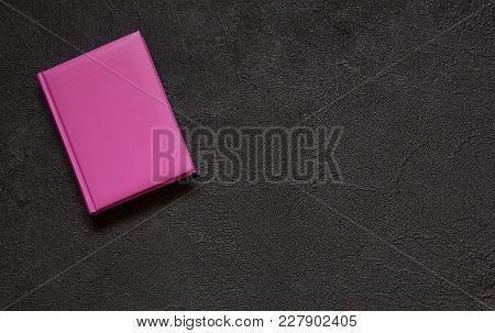 Lilac Notepad On Black Concrete Background. Abstract Cement Background In Vintage Style. Top View.