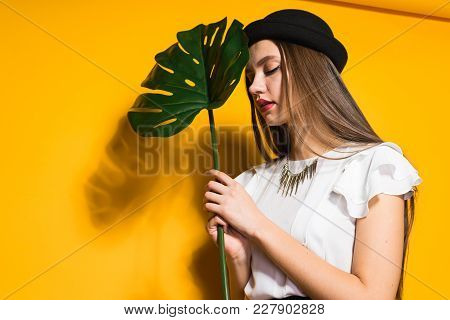 Beautiful Long-haired Girl In A Fashionable Black Hat Holds A Green Leaf, On A Yellow Background