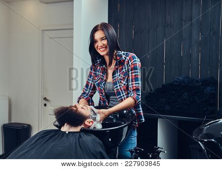 Professional Hairdresser Washing Clients Hair In A Barbershop.