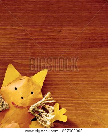 Handmade Orange Toy Cat On Red-brown Wooden Background As Template For Greeting Card Or Postcard. To