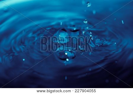 Abstract Background With Blue Liquid Ripples And Drops, And Light Reflection, Blurred Background
