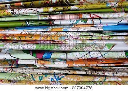 Stack Of Colorful Topographic Map For Orienteering Or Rogaining Sport As Horizontal Background. Conc