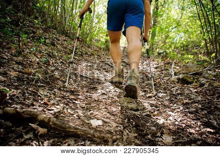 Active Runner Climbs Up The Mountain Using Special Equipment For Nordic Walking And Professional Sho