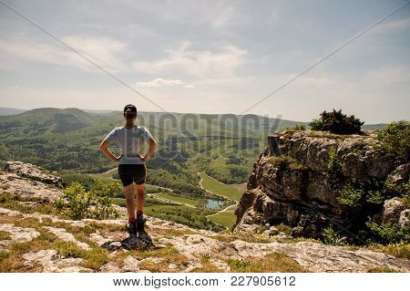 Muscular Woman In Sporty Uniform And Sneakers Is Walking Along The Rocky Mountains In The Background