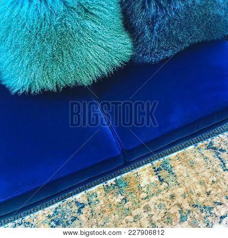 Luxurious Sheepskin Cushions Decorating A Blue Velvet Sofa.
