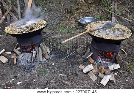 Cooking In The Outdoor Kitchen. Two Metal Barrels Use As A Wood-burning Stove With Wok Pans With Tof