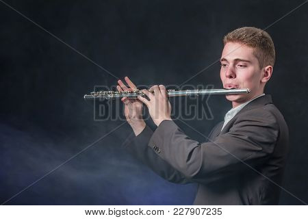 The Guy In The Gray Jacket Plays The Music On The Flute. Copy Space. Smoke Against A Dark Background