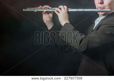 Copy Space. A Close-up Of A Flute In The Hands And On The Lips Of A Musician. The Guy Takes The Soun