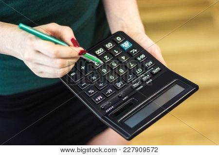 Woman Using A Calculator With A Pen In Her Hand, Calculating Financial Expense At Home Office