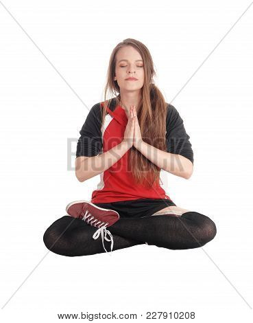 A Young Slim Woman Sitting In A Joga Pose With Her Eyes Closed And Meditating And Her Legs Crossed,