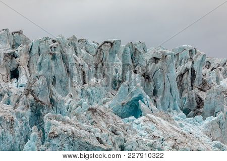 Close-up Of The Ice Of The Wahlenberg Glacier At Svalbard. Blue Ice With Cloudy Sky Above