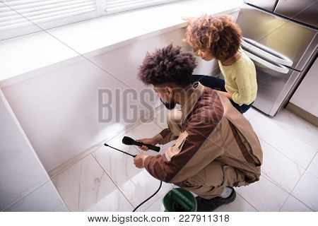 Young Male Pest Control Worker Using Torch While Spraying Insecticide On Window Sill