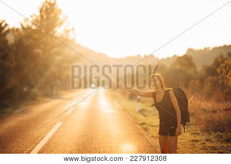Young Backpacking Adventurous Woman Hitchhiking On The Road.stopping A Car With A Thumb.travel Lifes