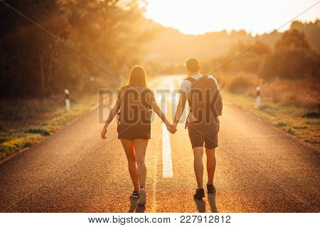 Young Backpacking Adventurous Couple Hitchhiking On The Road.adventure Of Life.travel Lifestyle.low