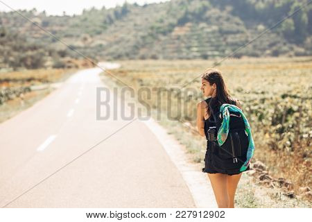 Young Backpacking Adventurous Woman Hitchhiking On The Road.traveling Backpacks Volume,packing Essen
