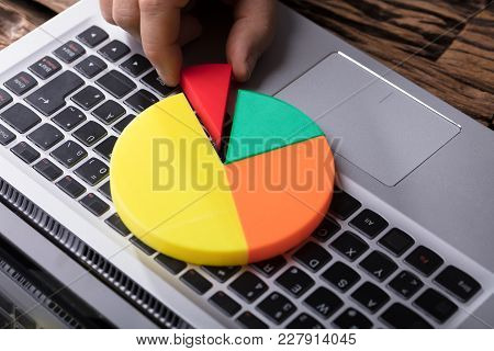 Close-up Of A Human Hand Placing Last Piece Into Pie Chart Over Laptop Keypad