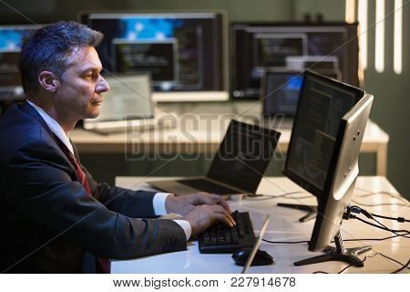 Side View Of A Mature Businessman Working On Multiple Computers In Office