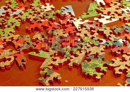 Puzzle Pieces Spread Across A Dark Wood Table In Fragments As They Wait For Assembly.
