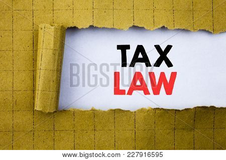 Tax Law. Business Concept For Taxation Taxes Rule Written On White Paper On Yellow Folded Paper.