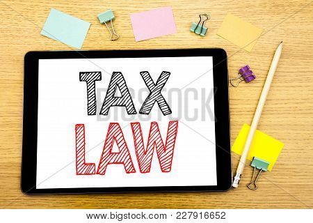 Writing Text Showing Tax Law. Business Concept For Taxation Taxes Rule Written On Tablet, Wooden Bac