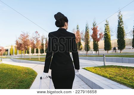 Triple Young Woman Stewardess In Uniform Goes On A Flight, With A Suitcase