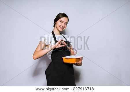 Smiling Young Girl Cook In Black Dress Prepares A Delicious Dish