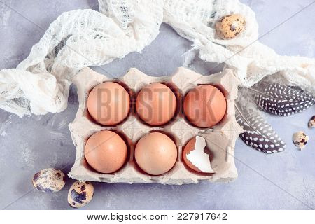 Fresh Brown Eggs In Craft Paper Tray On A Light Background With Feathers And Cloth. Ingredients For