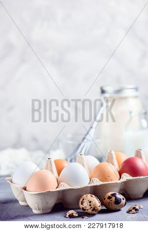 Fresh Brown And White Eggs In Craft Paper Tray On A Light Background With Quail Eggs, Whisk And Ingr