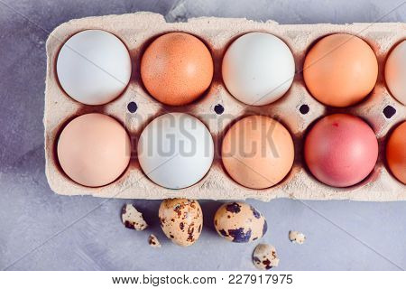 Brown Eggs In A Paper Carton Close-up On A Light Background With Quail Eggs, Whisk And Ingredients F